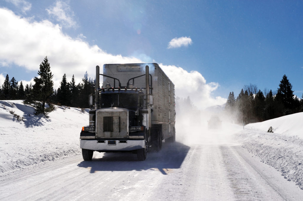 Big Rig and trailer driving down an icy and dangerous road with snow blowing behind the truck on a cold clear day in the mountains